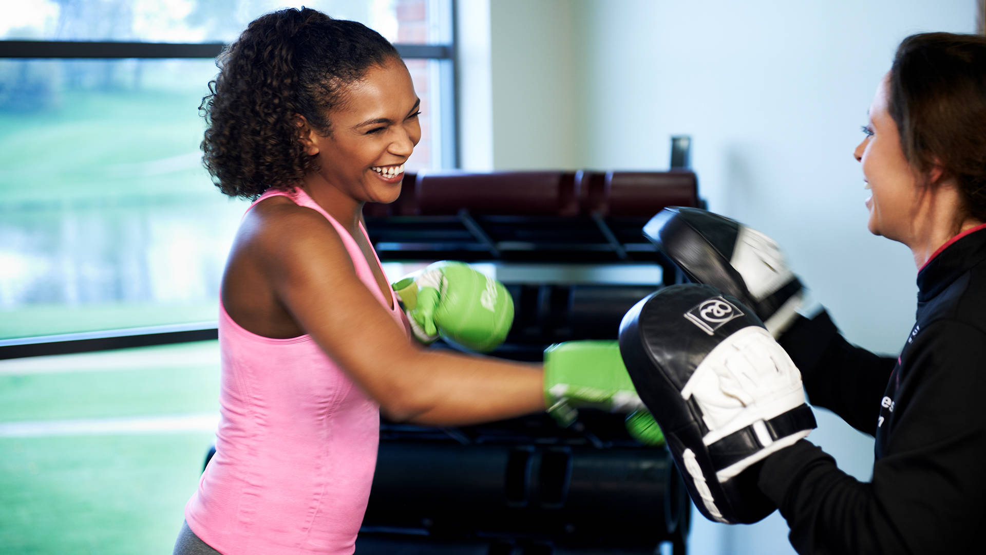 A female health club member and female personal training using boxing gloves and pads at Castle Royle